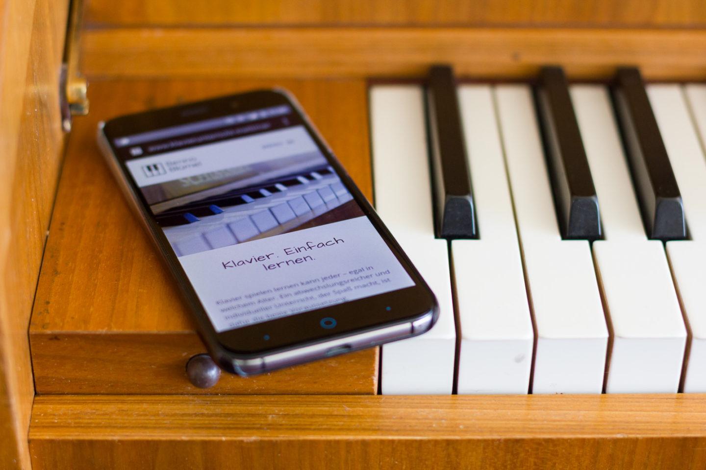 Kontakt & Anfahrt: Handy mit Website neben Klaviertasten