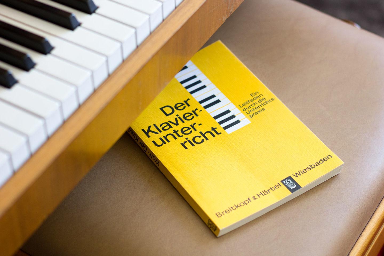 """Klavierunterricht: Buch """"Der Klavierunterricht"""" auf Klavierhocker"""